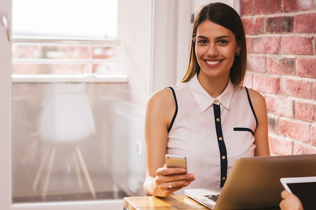 Lächelnde junge geschäftsfrau, die eine textnachricht im innenministerium sendet