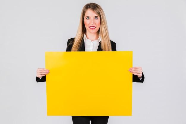 Lächelnde junge geschäftsfrau, die gelbes leeres plakat gegen grauen hintergrund hält