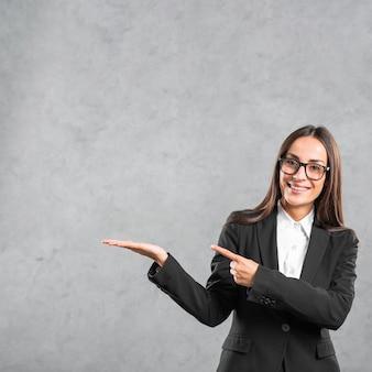 Lächelnde junge geschäftsfrau, die ihren finger in richtung zum darstellen des produktes zeigt