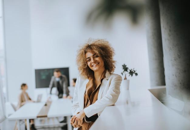 Lächelnde junge geschäftsfrau, die im modernen büro steht