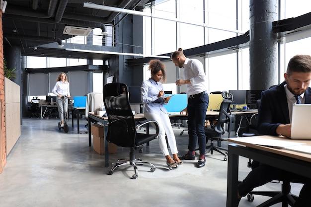 Lächelnde junge geschäftsfrau, die während ihrer arbeitspause einen roller durch ein großes modernes büro fährt.