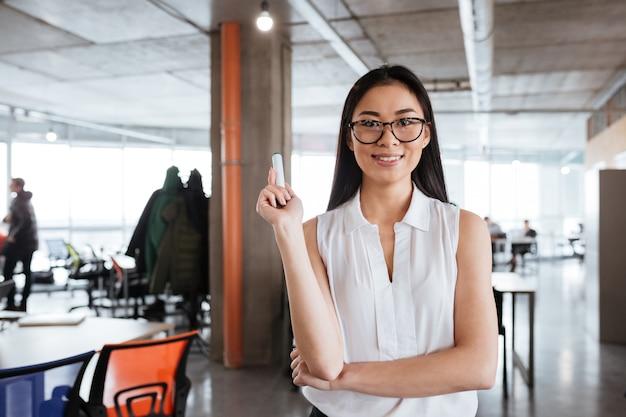 Lächelnde junge geschäftsfrau, die whiteboard merker im amt steht und hält