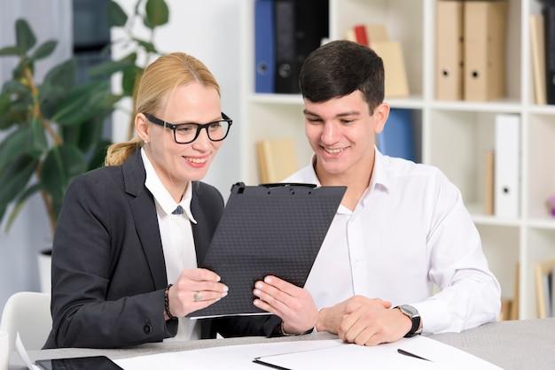 Lächelnde junge geschäftsfrau und geschäftsmann, die digitale tablette im büro betrachten