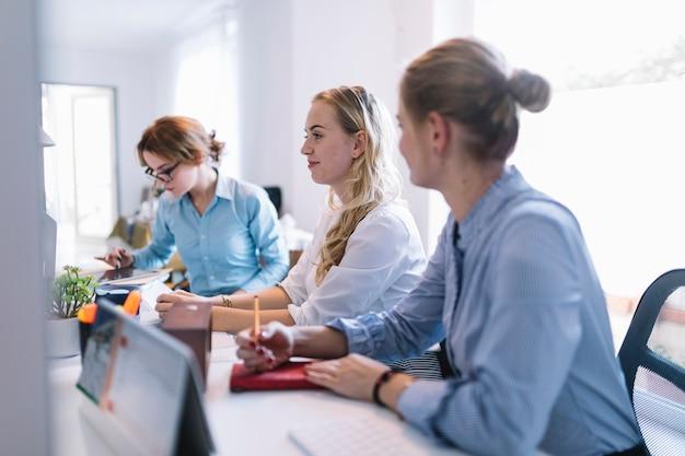 Lächelnde junge geschäftsleute, die in folge sitzen, arbeiten im büro