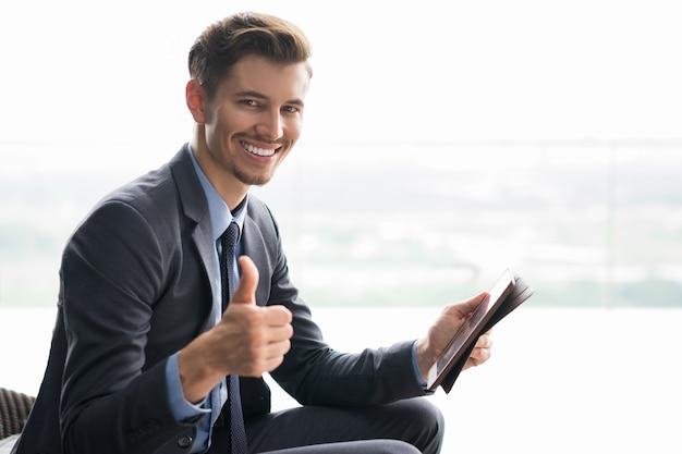 Lächelnde junge geschäftsmann mit daumen nach oben und tablet