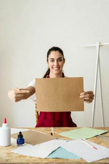 Lächelnde junge gestikulierende frau beim halten des braunen papiers