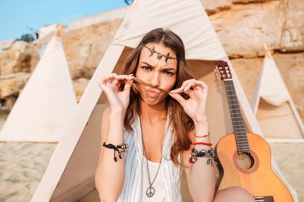 Lächelnde junge hippie-frau im wigwam am strand