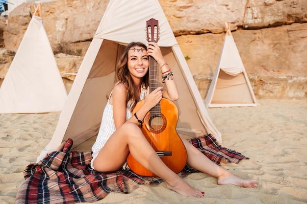 Lächelnde junge hippie-frau posiert mit gitarre am strandzelt