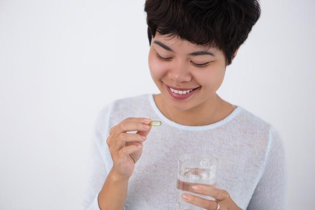 Lächelnde junge hübsche asiatische frau, die pille nimmt