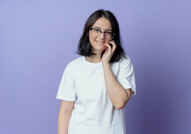 Lächelnde junge hübsche frau, die brille trägt hand auf wange setzt