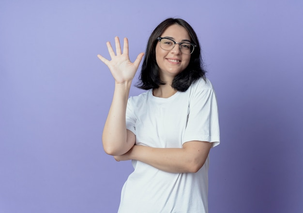 Lächelnde junge hübsche frau, die brille trägt, zeigt fünf mit der hand