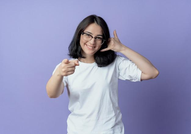 Lächelnde junge hübsche frau, die eine brille trägt, die anrufgeste tut und nach vorne zeigt