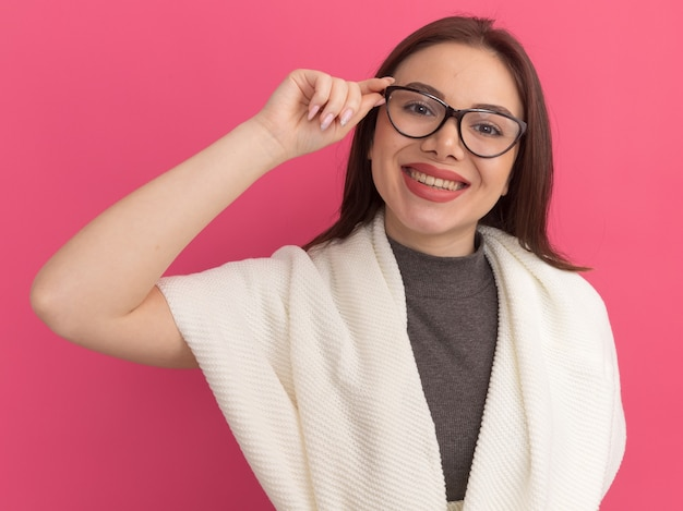 Lächelnde junge hübsche frau, die eine brille trägt und greift, isoliert auf rosa wand?
