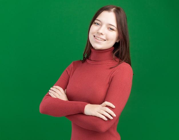 Lächelnde junge hübsche frau, die mit geschlossener haltung steht und nach vorne schaut, isoliert auf grüner wand mit kopierraum