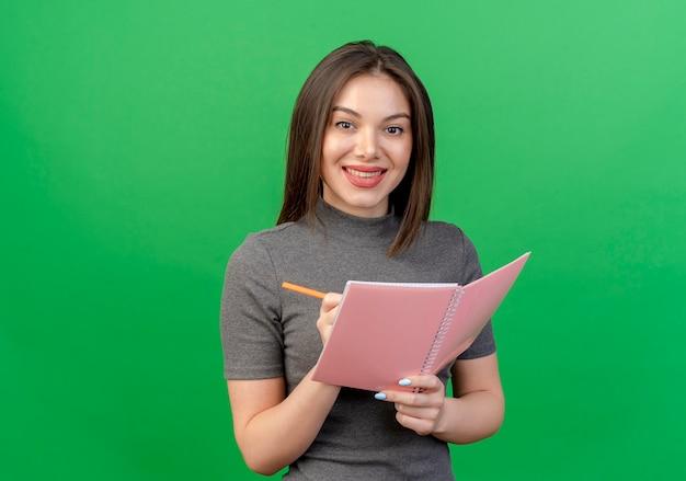 Lächelnde junge hübsche frau, die notizblock und stift hält, die bereit sind, lokalisiert auf grünem hintergrund mit kopienraum zu schreiben