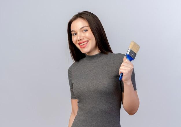 Lächelnde junge hübsche frau, die pinsel lokalisiert auf weißem hintergrund mit kopienraum hält