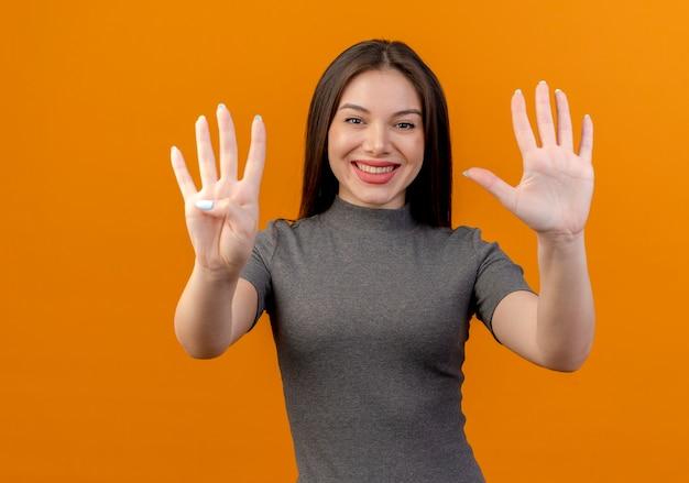Lächelnde junge hübsche frau, die vier und fünf mit auf orange lokalisierten händen zeigt