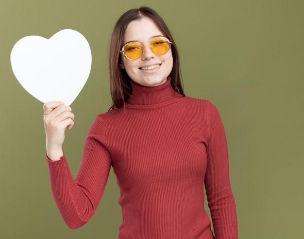 Lächelnde junge hübsche frau mit sonnenbrille mit herzschild auf der vorderseite isoliert auf olivgrüner wand