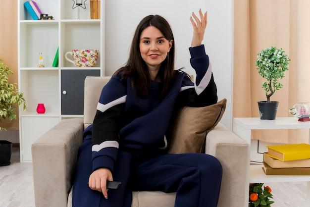 Lächelnde junge hübsche kaukasische frau, die auf sessel im entworfenen wohnzimmer hält, das fernbedienung hält und hand in der luft hält