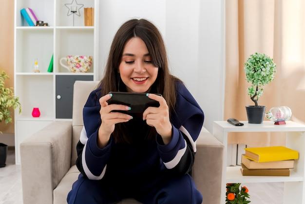 Lächelnde junge hübsche kaukasische frau, die auf sessel im gestalteten wohnzimmer unter verwendung ihres handys sitzt