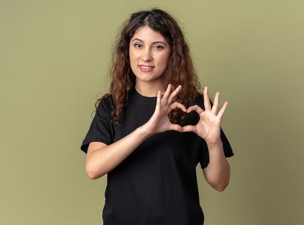 Lächelnde junge hübsche kaukasische frau, die herzzeichen tut