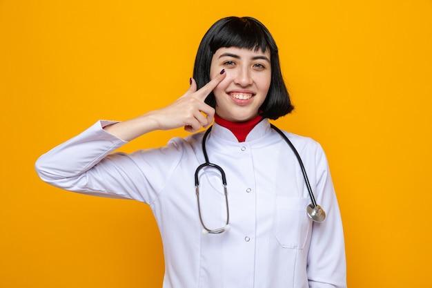Lächelnde junge hübsche kaukasische frau in arztuniform mit stethoskop, die den finger nah an ihrem auge hält
