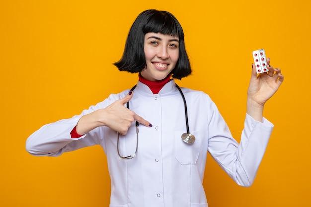 Lächelnde junge hübsche kaukasische frau in arztuniform mit stethoskop, die pillen hält und auf sich selbst zeigt