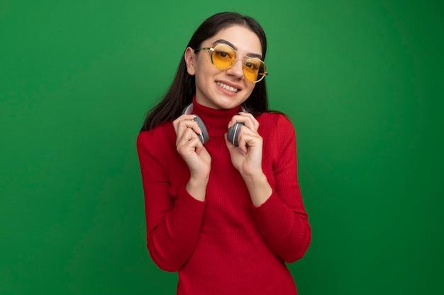 Lächelnde junge hübsche kaukasische frau mit sonnenbrille und kopfhörern am hals, die kopfhörer packt