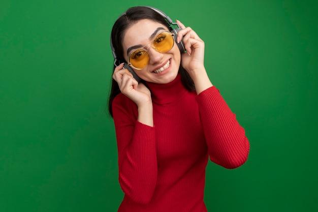 Lächelnde junge hübsche kaukasische frau mit sonnenbrille und kopfhörern, die kopfhörer greifen