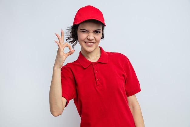 Lächelnde junge hübsche lieferfrau blinzelt mit den augen und gestikuliert ok