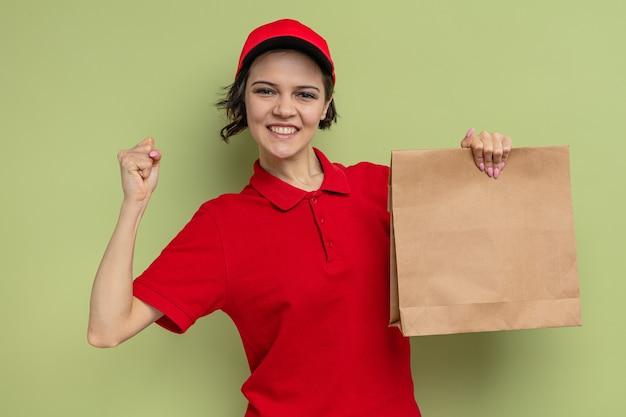 Lächelnde junge hübsche lieferfrau, die faust hält und lebensmittelverpackungen aus papier hält