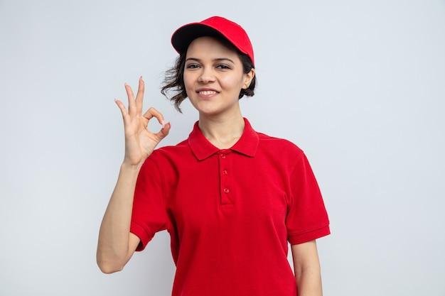 Lächelnde junge hübsche lieferfrau, die okayzeichen gestikuliert