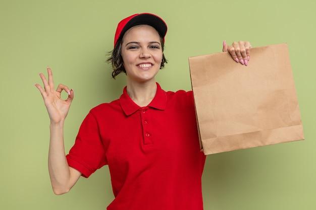 Lächelnde junge hübsche lieferfrau, die papierverpackungen für lebensmittel hält und ein ok-zeichen gestikuliert