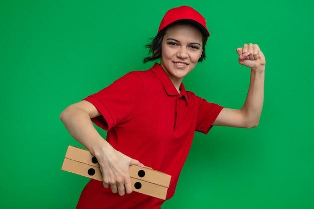 Lächelnde junge hübsche lieferfrau, die pizzakartons hält und so tut, als würde sie laufen