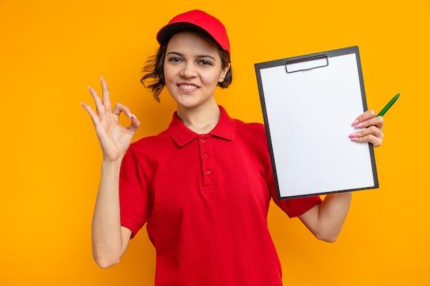 Lächelnde junge hübsche lieferfrau, die zwischenablage hält und ok-zeichen gestikuliert
