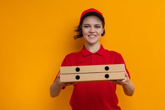Lächelnde junge hübsche lieferfrau hält pizzakartons