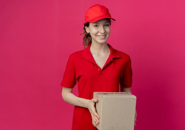 Lächelnde junge hübsche lieferfrau in roter uniform und kappe, die kartonbox lokalisiert auf purpurrotem hintergrund mit kopienraum hält