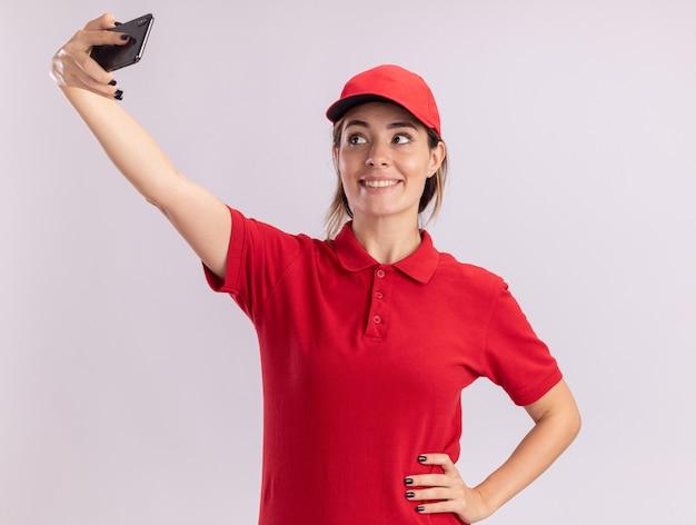 Lächelnde junge hübsche lieferfrau in uniform hält und schaut auf telefon, das selfie lokalisiert auf weißer wand nimmt