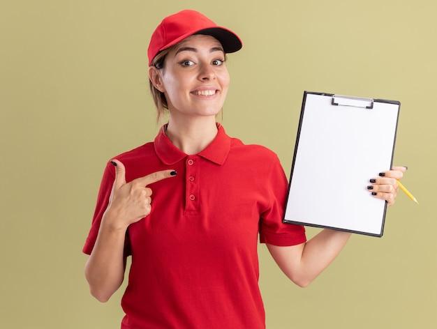 Lächelnde junge hübsche lieferfrau in uniform hält und zeigt auf zwischenablage lokalisiert auf olivgrüner wand