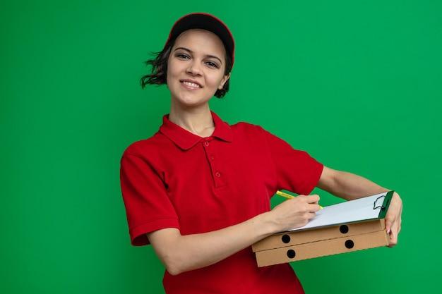 Lächelnde junge hübsche lieferfrau mit klemmbrett auf pizzakartons