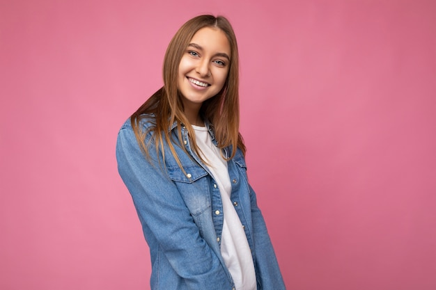 Lächelnde junge hübsche sexy dunkelblonde frau mit aufrichtigen gefühlen lokalisiert auf der hintergrundwand mit kopienraum, der lässiges weißes t-shirt und jeanshemd trägt. positives konzept