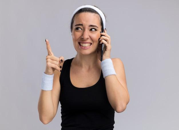 Lächelnde junge hübsche sportliche frau mit stirnband und armbändern, die am telefon spricht und auf die seite schaut, die nach oben zeigt, isoliert auf weißer wand mit kopierraum