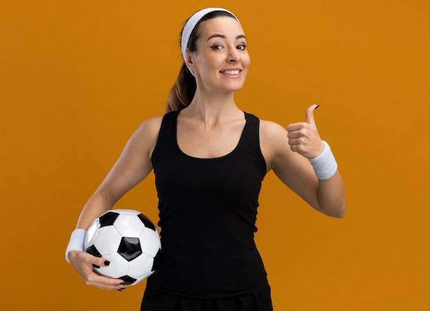 Lächelnde junge hübsche sportliche frau mit stirnband und armbändern, die einen fußball hält, der nach vorne schaut und den daumen isoliert auf der orangefarbenen wand zeigt