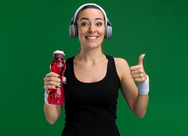 Lächelnde junge hübsche sportliche frau mit stirnband und armbändern mit kopfhörern, die eine wasserflasche halten und nach vorne schauen und den daumen einzeln auf grüner wand zeigen showing
