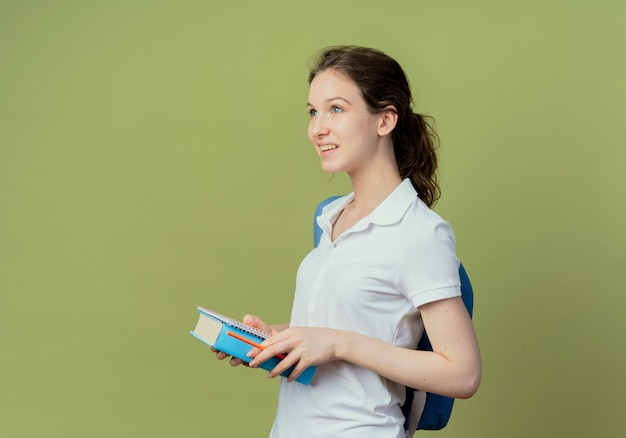 Lächelnde junge hübsche studentin, die eine rückentasche trägt, die in der profilansicht steht und einen notizblockstift und ein buch hält, das gerade schaut
