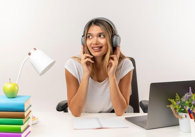 Lächelnde junge hübsche studentin, die kopfhörer trägt, sitzt am schreibtisch mit schulwerkzeugen, die musik hören, die seite mit den fingern auf kopfhörern lokalisiert auf weißer wand betrachtet