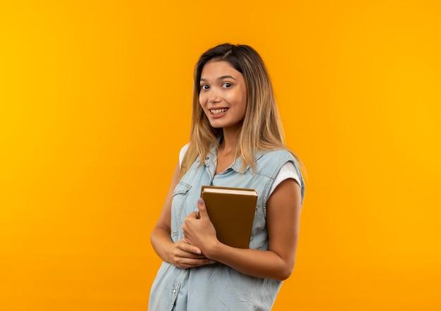 Lächelnde junge hübsche studentin, die rückentasche hält buch lokalisiert auf orange wand trägt