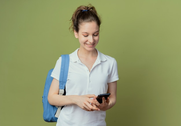 Lächelnde junge hübsche studentin, die rückentasche unter verwendung des mobiltelefons lokalisiert auf grünem hintergrund mit kopienraum trägt