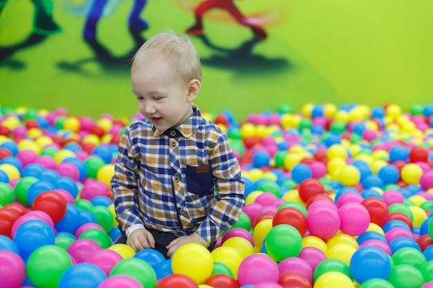 Lächelnde junge im pool mit bunten kugeln. familienerholung im kinderzentrum. lächelnde jungenspiele im spielzimmer. glückliche kindheit.