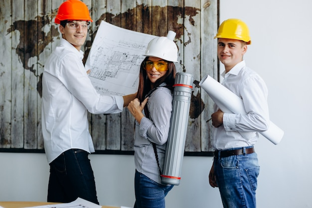 Lächelnde junge ingenieure, die an plänen im büro arbeiten